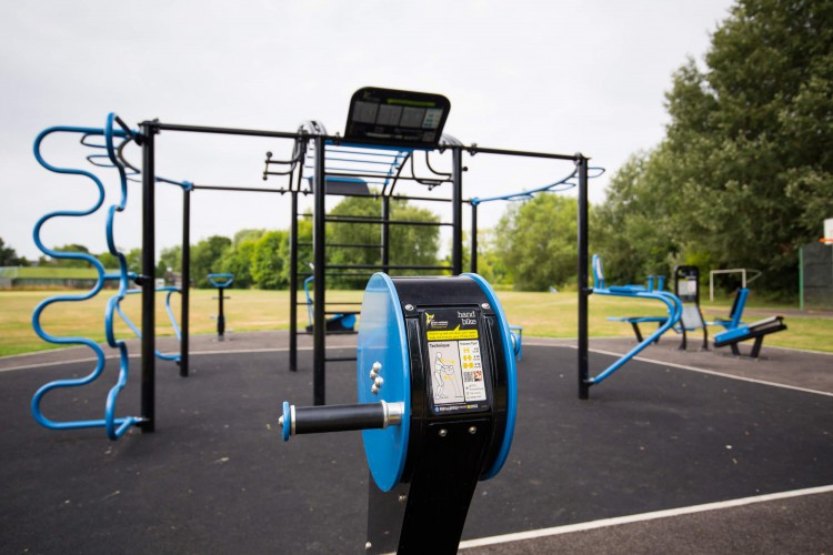 blue and black climbing frame and exercise machines in an open grassy area