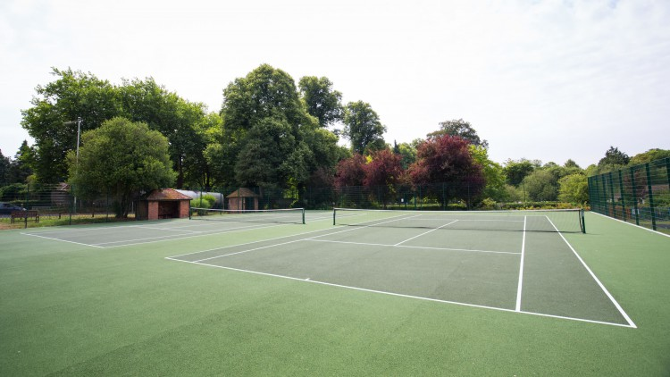 two beautiful astro tennis courts surrounded on 2 sides by trees